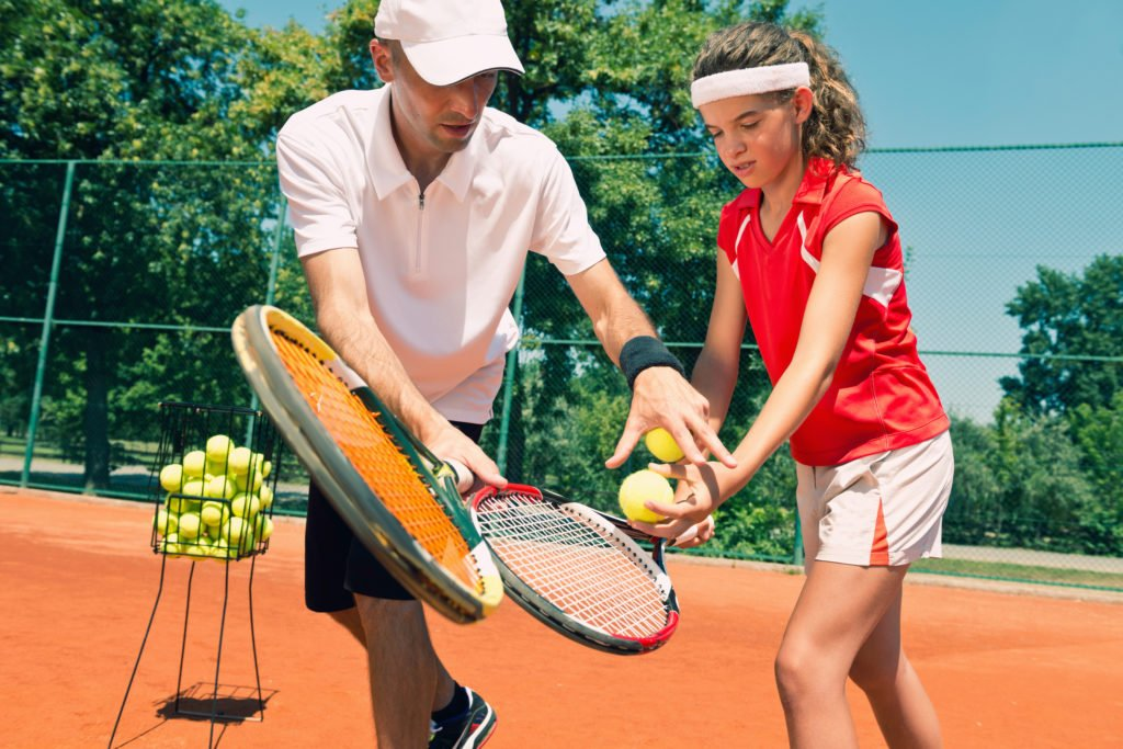 Tennis lesson - instructor working with teenager.